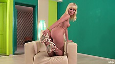 Blondie pulls her thong aside to have full access to her shaven slit