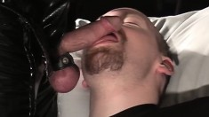 Rob has his hands bound and a latex covered man sticks his cock in his mouth
