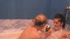 Young girlfriend gives her lover a fun time during a soapy bath