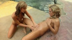 Gorgeous blonde lesbian babes play with each other by the pool