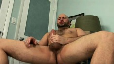 Bald headed stud massages his big balls and jerks off his large prick
