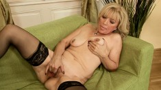 Hot blonde mature in black stockings has a young girl fisting her twat